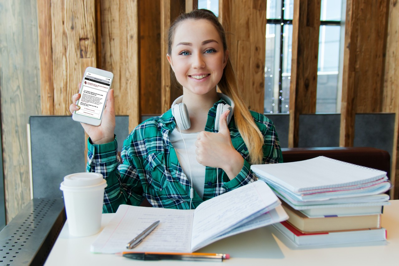 student studying and surrounded by books, giving a thumbs up while holding up phone to display for photo