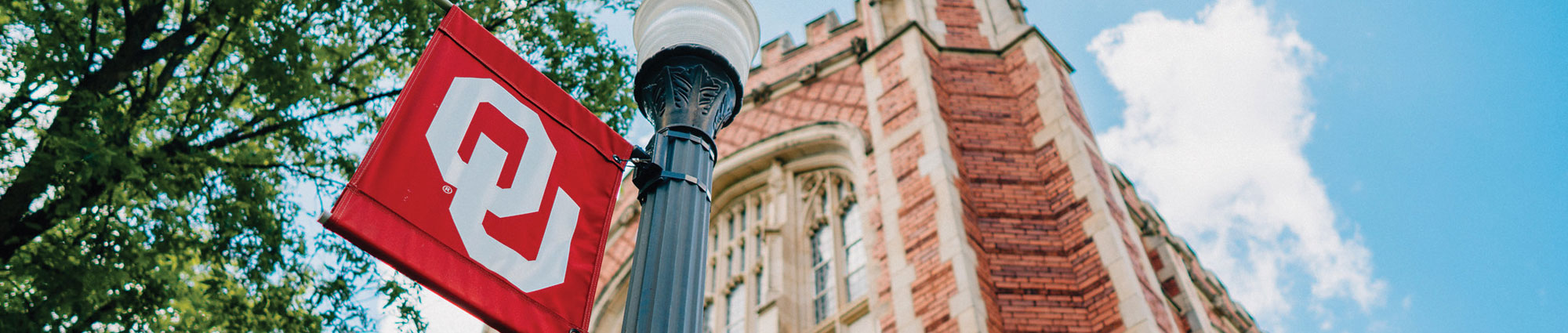 ou flag on lamp pole with brick building in the background