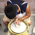 student working on potter's wheel